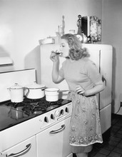 Young Woman In An Apron In Her Kitchen Tasting Her Food From A Pot