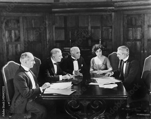Fotomural Group of men sitting with a young woman in a boardroom