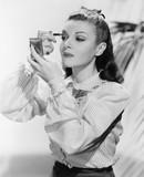 Młoda kobieta, patrząc w lustro i zakładanie makijażu - 104432281