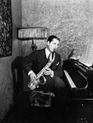 Man sitting at piano playing saxophone