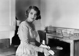 Young woman in her kitchen putting a pot into the oven  - 104434046