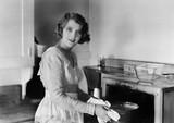 Młoda kobieta w jej kuchni stawia garnek w piekarnik - 104434046