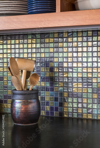 Detail Of Contemporary Upscale Home Kitchen Interior With Iridescent Gl Tile Backsplash Wall And Black Concrete