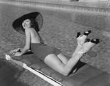 Woman sunbathing at pool  - 104436095