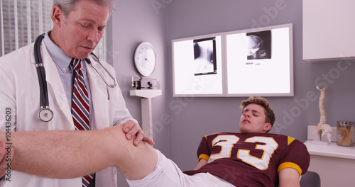 College sports athlete with mid aged doctor examining knee injur