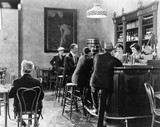 Men sitting around a counter in a bar  - 104439850
