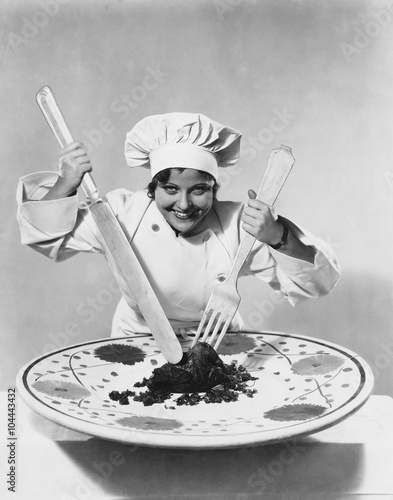 Fotografie, Obraz  Cook with food on oversize plate with oversize utensils