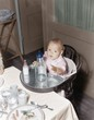 Baby in highchair with large and small bottles
