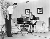 Salesperson demonstrates a vacuum cleaner to a housewife in her home  - 104446446