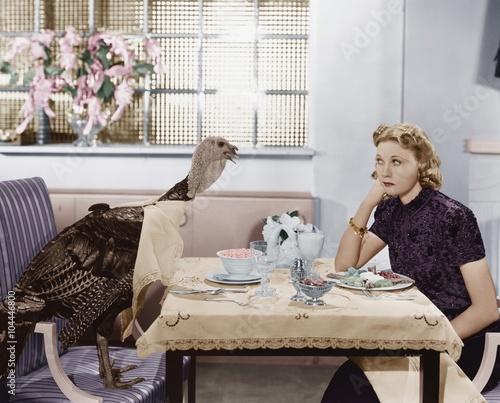 Woman eating meal at table with live turkey Slika na platnu
