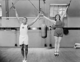 Athletes on rings in gym  - 104447657