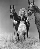 Cowgirl with two horses  - 104448296
