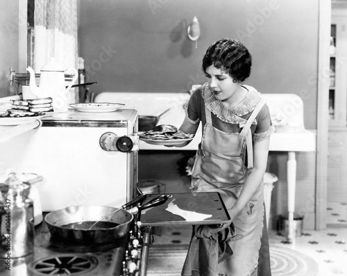 Obraz Young woman in an apron in her kitchen taking food out of the oven  - fototapety do salonu