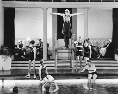 Photo  Young woman standing on a diving board surrounded by a group of people playing