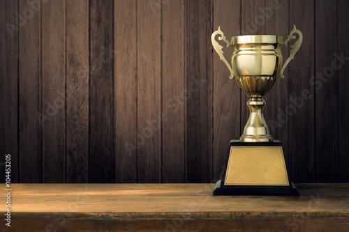 Fotografía  Trofeos colocados en un piso de madera con un espacio.
