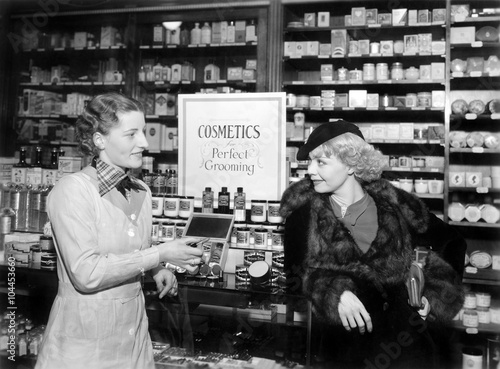 Photo Two women in a drug store looking at each other