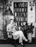 Young woman reading in her library  - 104455443