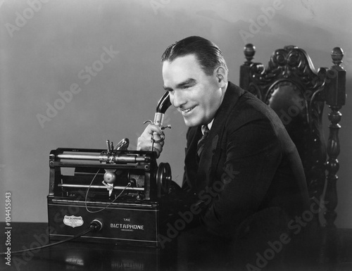 Canvas Smiling man using Dictaphone