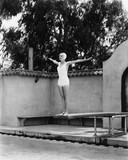 Woman on diving board at swimming pool  - 104457453