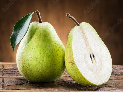 Obraz na plátně Pear fruit with leaf on wooden background.
