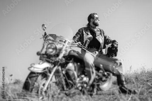 Fotografia  Portrait of a young man with beard sitting on his cruiser motorcycle and looking to the sun