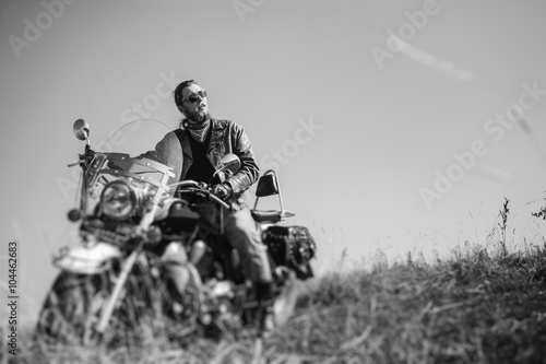 Cadres-photo bureau Motorise Portrait of a young man with beard sitting on his cruiser motorcycle. Biker is wearing leather jacket and blue jeans. Low point of view. Tilt shift lens blur effect. Black and white