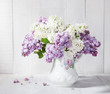 Lilac bouquet in ceramic jug against a white wooden wal