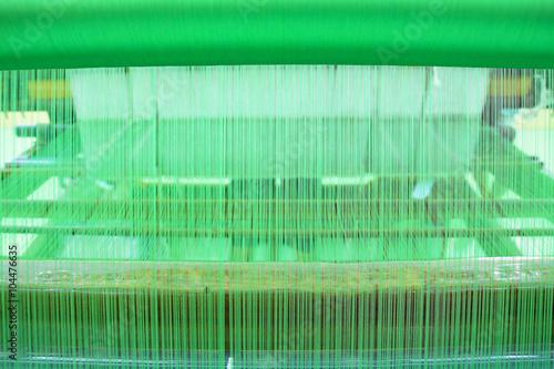 Fotografie, Obraz  Green yarn pattern is set up on the loom bench