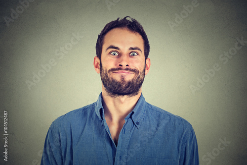 Photo  Crazy looking man making funny faces isolated on gray wall background