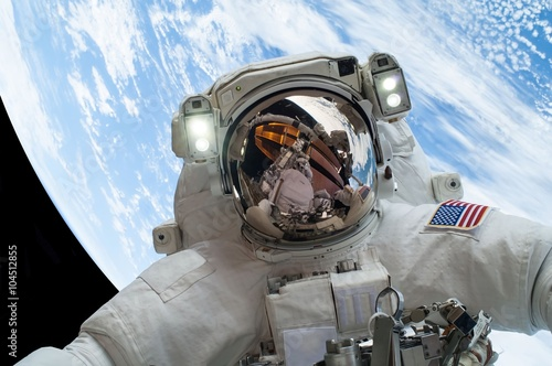 astronaut floating in space against the backdrop of earth (some elements courtesy of nasa).