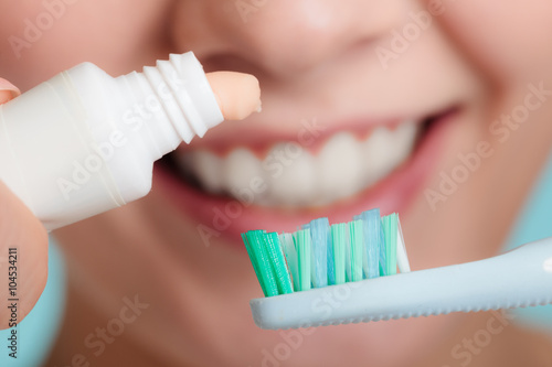 Woman putting toothpaste on toothbrush Canvas Print