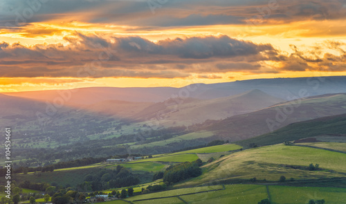 Garden Poster Light pink Golden sunlight shining on green British hills with dramatic clouds in the Peak District.