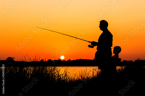 Fotografie, Obraz  Otec a syn rybaření v řece pozadí při západu slunce