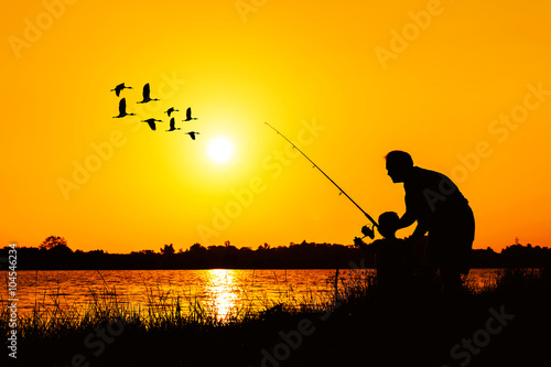 Fotobehang Jacht father and son fishing in the river sunset backgrond