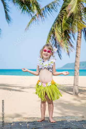 de78ce4e92fc Smiling little girl with face painting in Hawaiian costume. Fancy dress  party on the beach with palms.