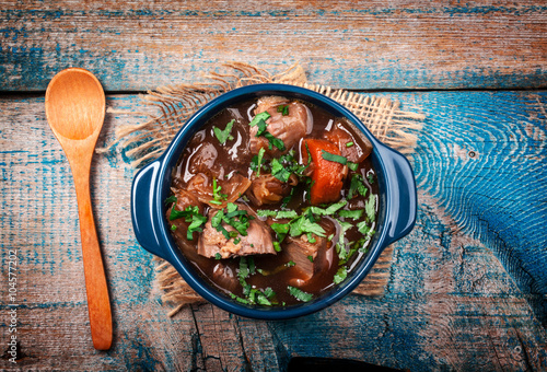 Fotografie, Obraz  Meat stew with vegetables and herbs on old wooden table