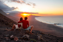 Young Couple Enjoying Beautiful Sunset Sitting Together On The Mountain With Great View On Cofete Coastline On Fuerteventura Island