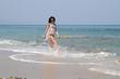 Long haired brunette in black bikini walking at the beach.