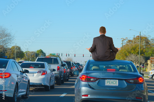 Fotografie, Obraz  A man is dealing with intense work rush hour traffic jam stress by getting relief doing yoga on top of his car in this humorous scene that shows PEACE on the license plate of the car he is sitting on