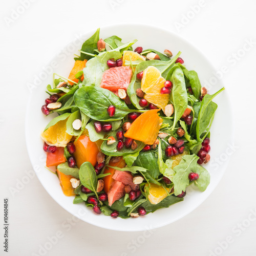 Fresh salad with fruits and greens on white background top view. Healthy food.
