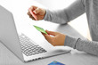 E-commerce concept. Woman with credit card and laptop, close up