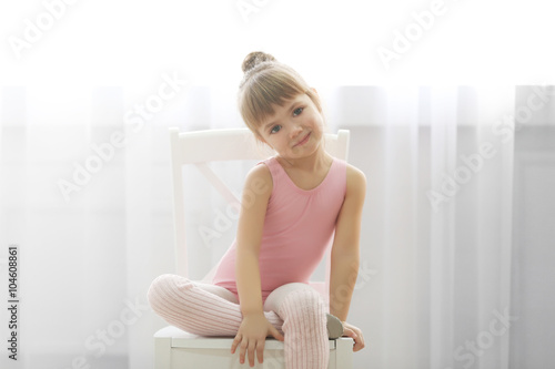 32e44d791b27 Little cute girl in pink leotard sitting on chair at dance studio ...