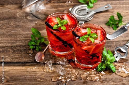 czerwony-napoj-z-lodem-lisci-miety-i-czarnymi-slomkami-na-drewnianym-stoliku