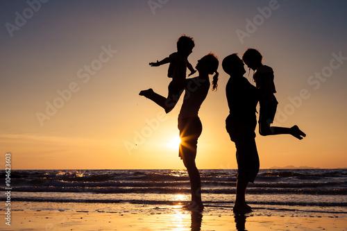 Fototapeta Silhouette of happy family who playing on the beach at the sunse obraz na płótnie