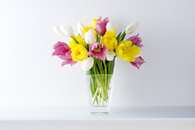 白い背景と棚と花瓶と3色のチューリップ