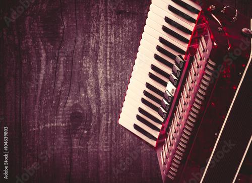 Fotografía  Parte de acordeón rojo sobre fondo gris madera