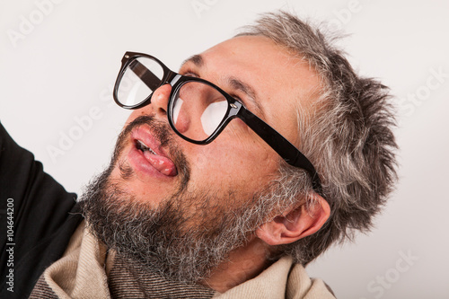 Photo  Crazy looking old man with grey beard nerd big glasses show tongue
