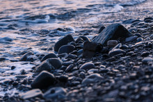 Pebbles On The Sea Shore At Sunset