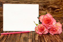 Three Roses With Blank Greeting Card And Pink Pencil On A Wooden