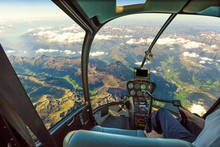 Helicopter Cockpit Flying On Mountain Landscape And Cloudy Sky, With Pilot Arm Driving In Cabin. Spectacular Aerial View Of Alps Mountain Chain.